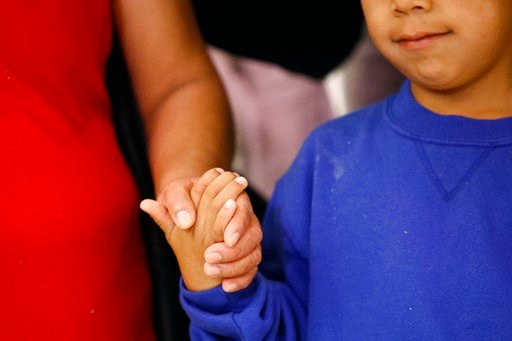(AP Photo/Patrick Semansky, File). In this Friday, June 22, 2018, file photo, a mother, left, and son, from Guatemala, hold hands during a news conference following their reunion in Linthicum, Md.
