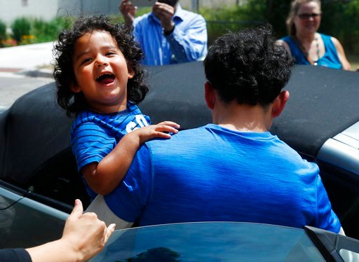 (AP Photo/Paul Sancya). Ever Reyes Mejia, of Honduras, carries his son to a vehicle after being reunited and released by United States Immigration and Customs Enforcement in Grand Rapids, Mich., Tuesday, July 10, 2018.