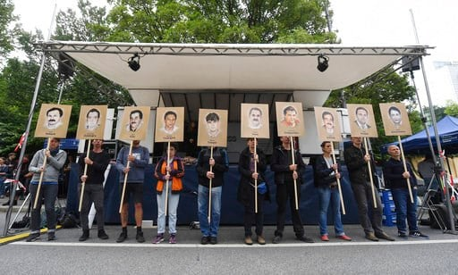 (Tobias Hase/dpa via AP). Demonstrators hold signs with people killed by the NSU outside the court in Munich, southern Germany, prior to the verdict Wednesday, July 11, 2018.