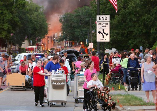 (Amber Arnold/Wisconsin State Journal via AP). People evacuate as they were told to move farther away the scene of an explosion in downtown Sun Prairie, Wis., Tuesday, July 10, 2018. The explosion rocked the downtown area of Sun Prairie, a suburb of Ma...