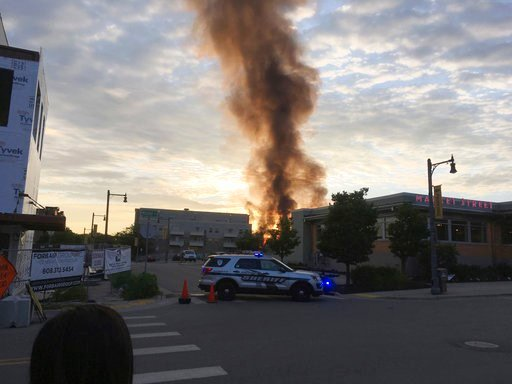 (AP Photo/Todd Richmond). A large plume of smoke from a massive fire is seen in Sun Prairie, Wis., Tuesday, July 10, 2018. Witnesses said the fire broke out after a loud boom Tuesday night shook the community. Police blocked off downtown streets from t...