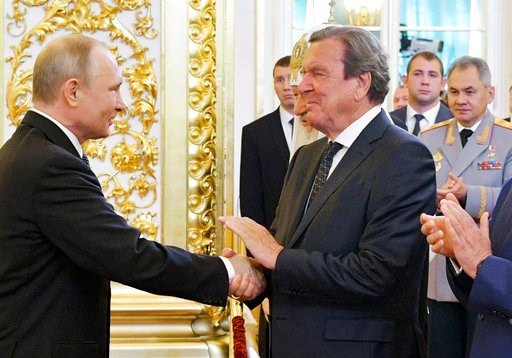 (Alexei Druzhinin, Sputnik, Kremlin Pool Photo via AP). FILE - in this May 7, 2018 file photo Vladimir Putin shakes hands with former German Chancellor Gerhard Schroeder during his inauguration ceremony as new Russia's president in the Grand Kremlin Pa...