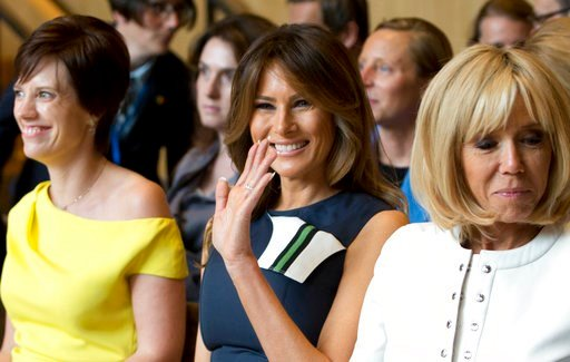 (AP Photo/Virginia Mayo). U.S. first lady Melania Trump, center, waves as she prepares to listen to a concert at the Queen Elisabeth Music Chapel in Waterloo, Belgium, during a spouses program on the sidelines of the NATO summit on Wednesday, July 11, ...