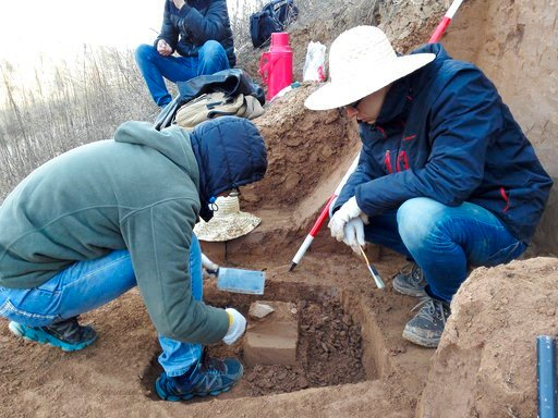 (Zhaoyu Zhu via AP). In this Sunday, Dec. 10, 2017 photo provided by Zhaoyu Zhu, scientists examine a pointed piece of quartzite rock that was unearthed from the oldest layer of dirt at a site in the Loess Plateau in China. In a report released on Wedn...