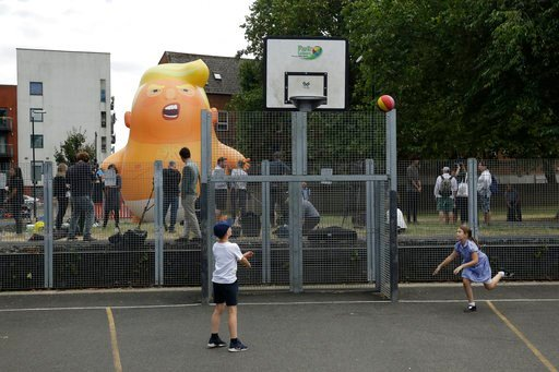 (AP Photo/Matt Dunham). In this photo taken on Tuesday, July 10, 2018, children play basketball in the foreground as a six-meter high cartoon baby blimp of U.S. President Donald Trump stands inflated during a practice session in Bingfield Park, north L...