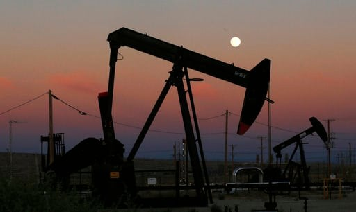 (AP Photo/Gary Kazanjian, File). FILE - In this June 8, 2017, file photo, oil derricks are busy pumping as the moon rises near the La Paloma Generating Station in McKittrick, Calif. The U.S. is on pace to leapfrog both Saudi Arabia and Russia as the wo...