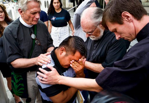 (AP Photo/Richard Vogel). Hermelindo Che Coc, of Guatemala, kneels as Father Tom Carey, left, Rev. David Farley and Rev. Matthias Peterson-Brandt, right, pray over him before a required check-in with immigration enforcement authorities on Tuesday, July...