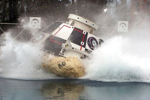 (David C. Bowman/NASA via AP). In this Feb. 9, 2016 photo made available by NASA, a mockup of Boeing's CST-100 Starliner spacecraft, in development in partnership with NASA's Commercial Crew Program, splashes into a 20-foot-deep basin at NASA's Langley...
