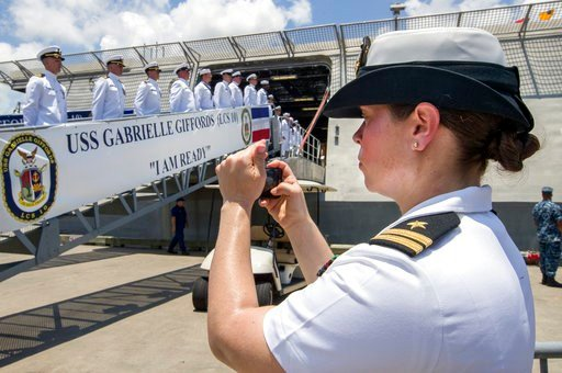 (Stuart Villanueva/The Galveston County Daily News via AP, File). FILE - In this June 10, 2017 file photo, U.S. Navy Lt. Miranda Williams photographs sailors as they board the USS Gabrielle Giffords during a commissioning ceremony in Galveston, Texas. ...