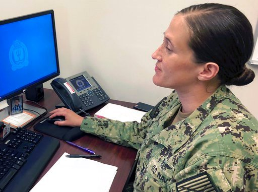 (AP Photo/Jennifer McDermott). U.S. Navy Legalman First Class Tamatha Schulmerich works at her desk at the Naval War College, Wednesday, July 11, 2018, in Newport, R.I. The Navy said Tuesday it will let women sailors sport ponytails and other longer ha...