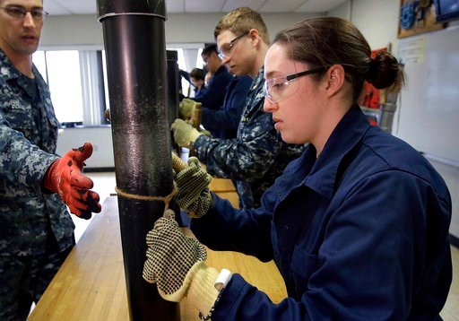 (AP Photo/Steven Senne, File). FILE - In this April 26, 2017 file photo, U.S. Navy Ensign Megan Stevenson, right, of Raymond, Maine, trains at patching high-pressure pipe leaks during a class at the Naval Submarine School, in Groton, Conn. The Navy sai...