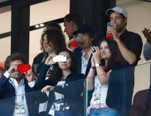 (AP Photo/Alastair Grant). Singer Mick Jagger of the Rolling Stones, in black baseball hat, drinks a pint during the semifinal match between Croatia and England at the 2018 soccer World Cup in the Luzhniki Stadium in, Moscow, Russia, Wednesday, July 11...