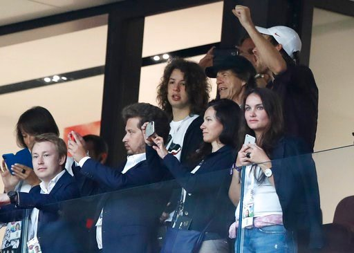 (AP Photo/Alastair Grant). Singer Mick Jagger of the Rolling Stones, in black baseball hat, smiles during the semifinal match between Croatia and England at the 2018 soccer World Cup in the Luzhniki Stadium in, Moscow, Russia, Wednesday, July 11, 2018.