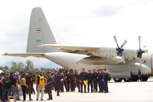 (AP Photo/Vincent Thian). Thai Navy SEALs and military personnel take a group picture before they board a plane at the airport in Chiang Rai, northern Thailand, Thursday, July 12, 2018.
