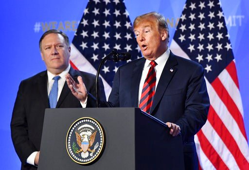 (AP Photo/Geert Vanden Wijngaert). U.S. President Donald Trump is flanked by U.S. Secretary of State Mike Pompeo, left, as he speaks during a press conference after a summit of heads of state and government at NATO headquarters in Brussels, Belgium, Th...