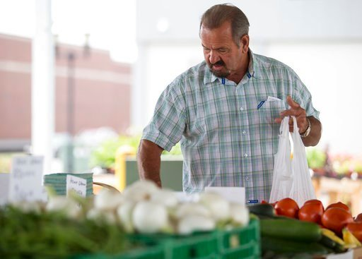 (Ellen O'Nan/The Paducah Sun via AP, File). FILE- In this June 13, 2018, file photo, Bob Harris carefully selects which tomatoes to buy at Paducah, Kentucky's Downtown Farmers' Market. On Thursday, July 12, the Labor Department reports on U.S. consumer...