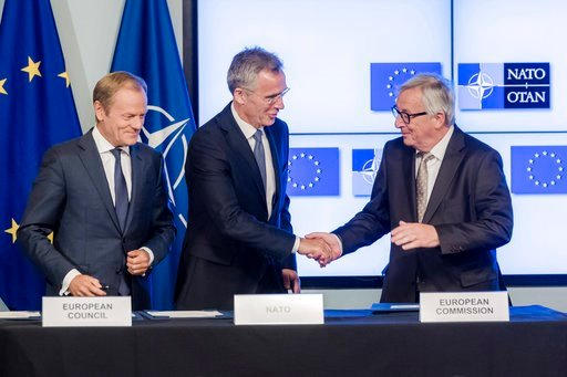 (AP Photo/Geert Vanden Wijngaert). European Council President Donald Tusk, left, European Commission President Jean-Claude Juncker, right, and NATO Secretary General Jens Stoltenberg shake hands after the signature of the second EU NATO Joint Declarati...