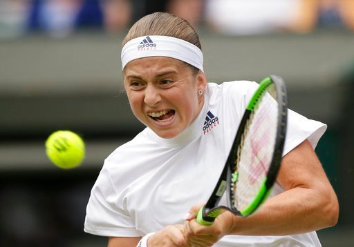 (AP Photo/Tim Ireland). Jelena Ostapenko of Latvia returns the ball to Dominika Cibulkova of Slovakia during their women's quarterfinal match at the Wimbledon Tennis Championships in London, Tuesday July 10, 2018.