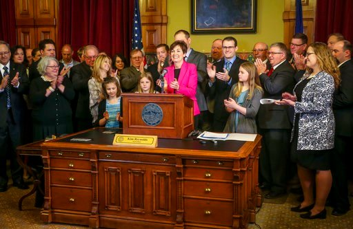 (Rodney White/The Des Moines Register via AP). In this April 2, 2018 photo, Gov. Kim Reynolds and others applaud after she signed a bill allowing unregulated health plans at the Iowa Statehouse in Des Moines, Iowa. Reynolds has touted her legislation a...