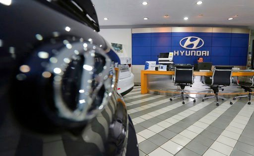 (AP Photo/Ahn Young-joon, File). FILE - In this Jan. 25, 2018 file photo, an employee of Hyundai Motor Co. waits for customers at the company's showroom in Seoul, South Korea. Hyundai Motor Co.'s labor union said Thursday, July 12, 2018, steep auto tar...