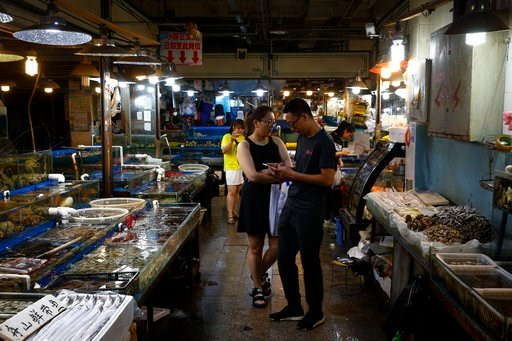 "(AP Photo/Andy Wong). A Chinese couple shop for seafoods at the Jingshen seafood market in Beijing, Thursday, July 12, 2018. China's government vowed on Wednesday to take ""firm and forceful measures"" as the U.S. threatened to expand tariffs to thousand..."