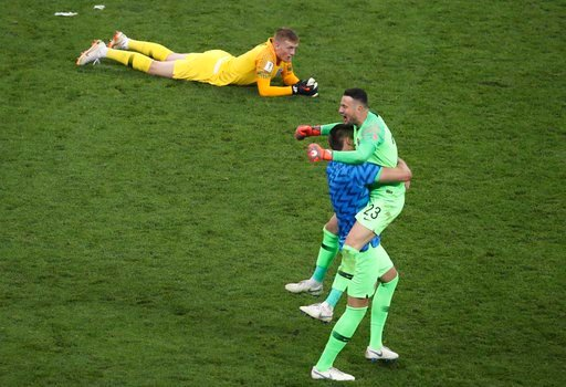 (AP Photo/Thanassis Stavrakis). England goalkeeper Jordan Pickford lies down on the pitch as Croatia goalkeeper Danijel Subasic, right, celebrates at the end of the semifinal match between Croatia and England at the 2018 soccer World Cup in the Luzhnik...