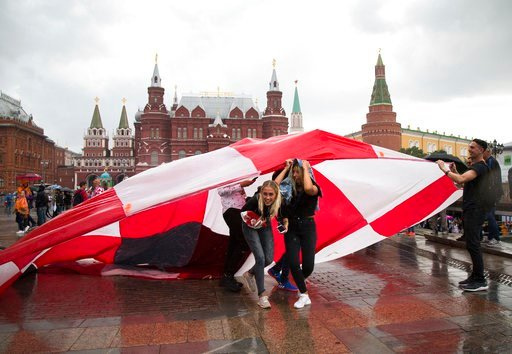 (AP Photo/Alexander Zemlianichenko). Soccer fans use a giant Croatian national flag as a shelter during the rain at Manezh Square near Red Square ahead of the semifinal soccer match between Croatia and England during the 2018 soccer World Cup at the Lu...