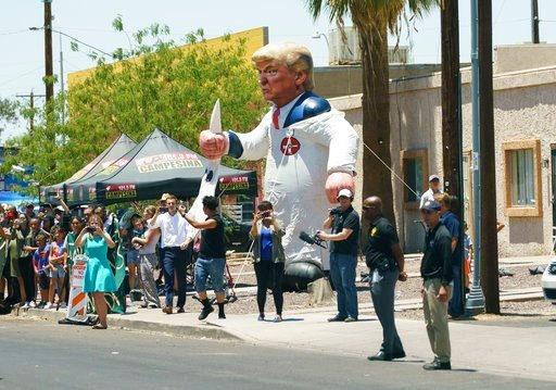 (AP Photo/Carolyn Kaster). Protesters place a large inflatable balloon in the likeness of President Donald Trump dressed in a Ku Klux Klan sheet across the street from Southwest Key Campbell, a shelter for children that have been separated from parents.