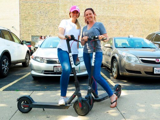 (AP Photo/Ivan Moreno). In this Wednesday, July11, 2018 photo, Kirby Bridges, left, and Megan Garlington pose with the Bird scooters they were taking for an afternoon ride in Milwaukee. Milwaukee is suing California-based Bird to stop the company from ...