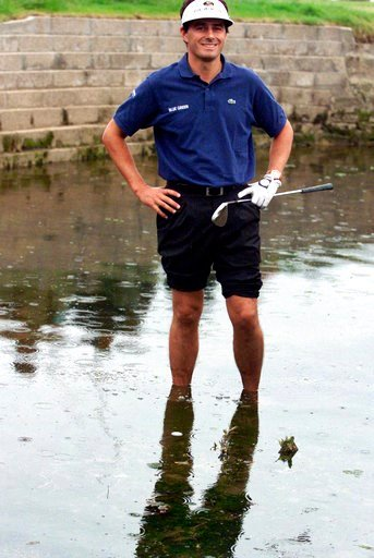 (AP Photo/File). FILE - In this July 18, 1999, file photo, France's Jean Van de Velde smiles as he stands in the water of the Barry Burn that crosses the 18th fairway to see if his ball, bottom center, was playable during the final round of the 128th B...