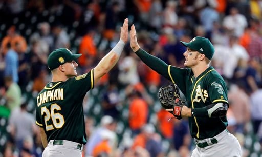 (AP Photo/David J. Phillip). Oakland Athletics' Matt Chapman (26) and Mark Canha celebrate after a baseball game against the Houston Astros Thursday, July 12, 2018, in Houston. The Athletics won 6-4.