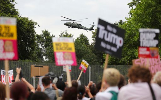 (Gareth Fuller/PA via AP). A US presidential helicopter lands in the grounds of the US ambassador residence in Regent's Park, London, while demonstrators protest against the visit to the UK., Thursday July 12, 2018. Trump will get the red carpet treatm...