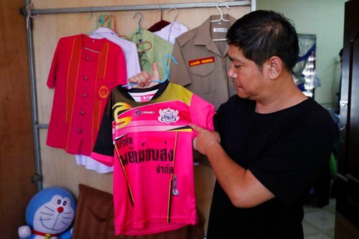 (AP Photo/Vincent Thian). Banphot Konkum, father of Duangpetch Promthep, shows his son's soccer jersey during an interview at their home in Mae Sai district, Chiang Rai province, northern Thailand, Friday, July 13, 2018. Banphot told The Associated Pre...