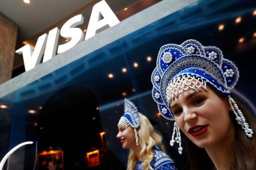 (AP Photo/Rebecca Blackwell). In this July 5, 2018 photo, women wearing traditional head dresses wait to greet Visa cardholders who won trips to the 2018 soccer World Cup, at the Marriott Novy Arbat Hotel, taken over by visa for the duration of the Wor...