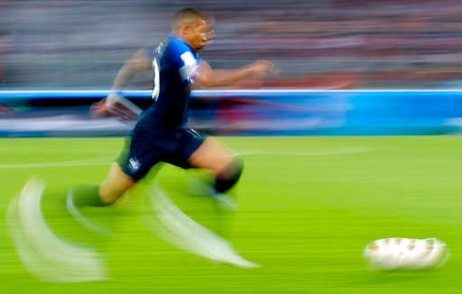 (AP Photo/Petr David Josek). In this photo taken with slow shutter speed France's Kylian Mbappe runs with the ball during the semifinal match between France and Belgium at the 2018 soccer World Cup in the St. Petersburg Stadium, in St. Petersburg, Russ...