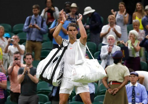 (AP Photo/Kirsty Wigglesworth). Rafael Nadal of Spain leaves the court after play was suspended in his men's singles semifinals match against Serbia's Novak Djokovic at the Wimbledon Tennis Championships, in London, Saturday July 14, 2018.