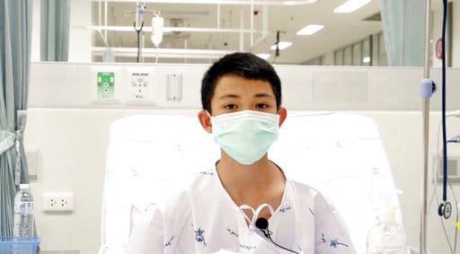 (Chiang Rai Prachanukroh Hospital via AP). This image made from a video taken on July 13, 2018 and released by Chiang Rai Prachanukroh Hospital, shows Duangpetch Promthep, one of the 12 boys rescued from the flooded cave, in their hospital room at Chia...