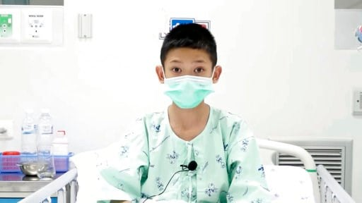 (Chiang Rai Prachanukroh Hospital via AP). This image made from a video taken on July 13, 2018 and released by Chiang Rai Prachanukroh Hospital, shows Monkol Boompeam, one of the 12 boys rescued from the flooded cave, in their hospital room at Chiang R...