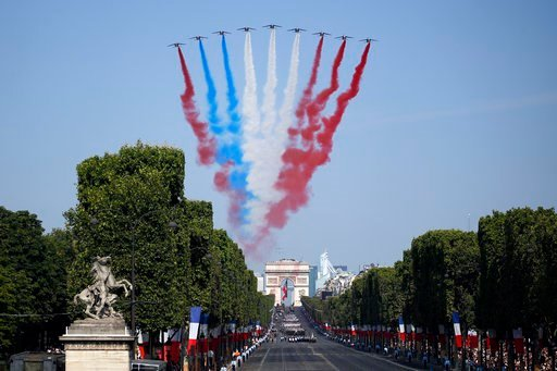(AP Photo/Francois Mori). French Alphajets of the Patrouille de France fly over the Champs Elysees avenue, with the Arc de Triomphe in background, during the Bastille Day parade in Paris, France, Saturday, July 14, 2018. France's military is marching t...