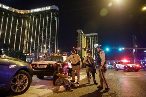 (AP Photo/John Locher, File). FILE - In this Oct. 1, 2017 file photo, police officers stand at the scene of a mass shooting near the Mandalay Bay resort and casino on the Las Vegas Strip, in Las Vegas. More police body-worn cameras made public Wednesda...