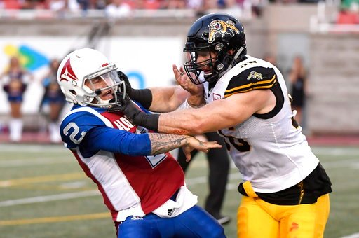 (Paul Chiasson/The Canadian Press via AP). Montreal Alouettes quarterback Johnny Manziel (2) is hit by Hamilton Tiger-Cats defensive end Jason Neill (96) during the first half of a Canadian Football League game Friday, Aug. 3, 2018, in Montreal.