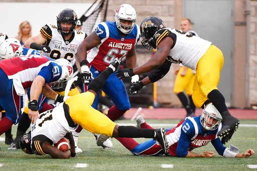 (Paul Chiasson/The Canadian Press via AP). Montreal Alouettes quarterback Johnny Manziel (2) makes a tackle after throwing an interception to Hamilton Tiger-Cats linebacker Larry Dean (11) during the first half of a Canadian Football League game Friday...