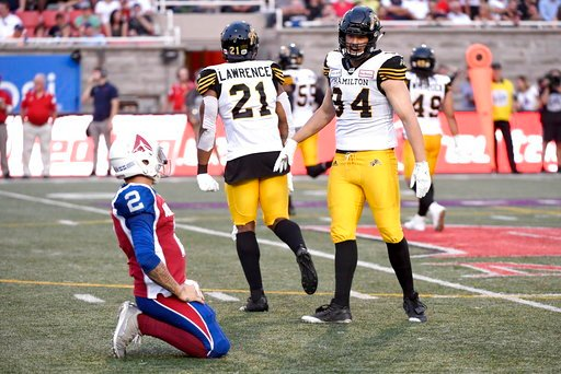 (Paul Chiasson/The Canadian Press via AP). Hamilton Tiger-Cats defensive end Justin Capicciotti (94) and linebacker Simoni Lawrence (21) celebrate a pass interception as Montreal Alouettes quarterback Johnny Manziel (2) kneels during the first half of ...