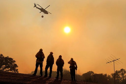 Firefighters stand watch on a roof as a wildfire sweeps through the area near Lakeport Calif. Thursday