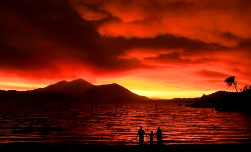 (Kent Porter/The Press Democrat via AP). Evacuees from Lucerne, from left, Ken Bennett with Ember Reynolds, 8, and Lisa Reynolds watch the sunset as smoke from the Ranch Fire rises into the sky at Austin Park Beach in California's Clearlake.