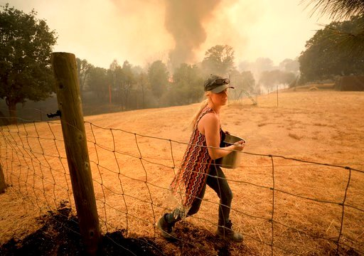 (Kent Porter/The Press Democrat via AP). Crystal Easter uses a pot of water to put out spot fires around her home, as her neighbor's home burns to the ground in the background, Monday, Aug. 6, 2018, in Spring Valley, Calif.