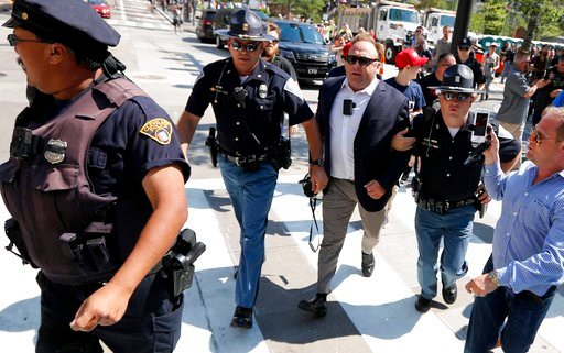 (AP Photo/John Minchillo, File). FILE - In this Tuesday, July 19, 2016 file photo, Alex Jones, center right, is escorted by police out of a crowd of protesters outside the Republican convention in Cleveland. Facebook says it has taken down four pages b...