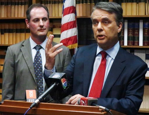 (AP Photo/John Hanna, File). FILE - In this May 30, 2018, file photo, Kansas Gov. Jeff Colyer, right, answers a question from reporters as Lt. Gov. Tracey Mann, left, listens during a news conference in Topeka, Kan. Colyer and immigration hardliner Kri...