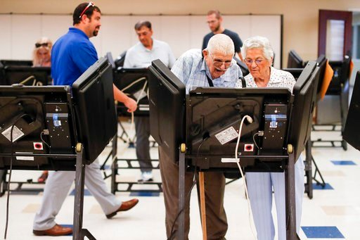 (AP Photo/John Minchillo). Voters cast their ballots among an array of electronic voting machines in a polling station at the Noor Islamic Cultural Center, Tuesday, Aug. 7, 2018, in Dublin, Ohio. Two-term state Sen. Troy Balderson, is fighting off a st...