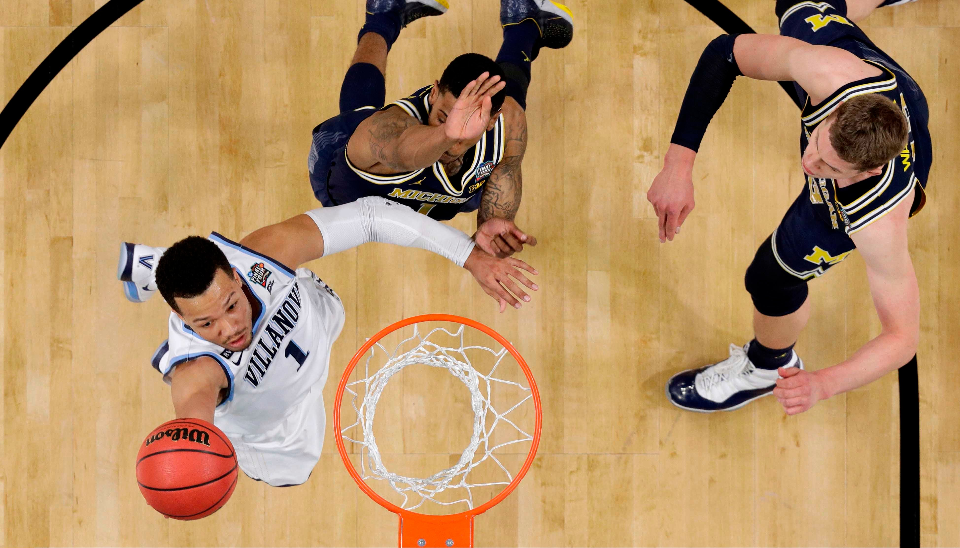 Villanova guard Jalen Brunson, left, drives to the basket over Michigan defenders Charles Matthews, center, and Moritz Wagner, right, during the championship game of the Final Four NCAA college basketball tournament, on April 2, 2018. (AP Photo/Eric Gay)